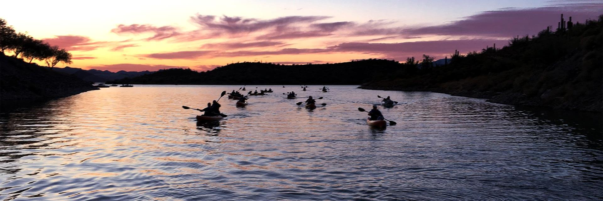 A group of kayakers on the water at sunset
